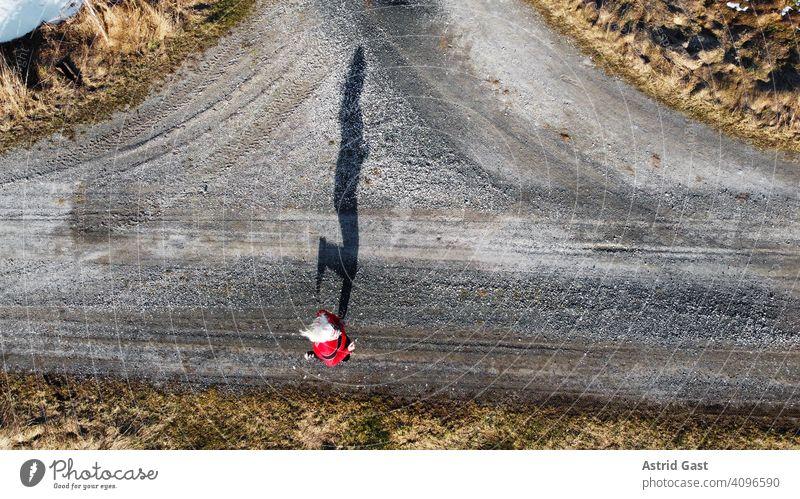 Luftaufnahme mit einer Drohne von einer Joggerin auf einer Straße mit Schatten luftaufnahme drohnenfoto frühling sport joggen frau joggerin laufen rennen straße