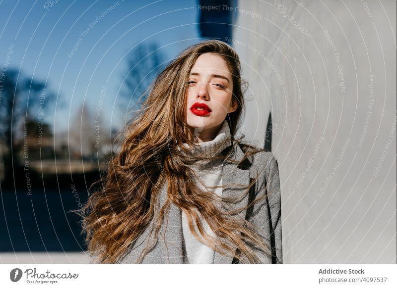 Junge Frau im Mantel an windigem Tag stylisch Straße Wand Großstadt Gebäude urban Mode cool jung Model Outfit warm Wetter Außenseite Dame lange Haare trendy
