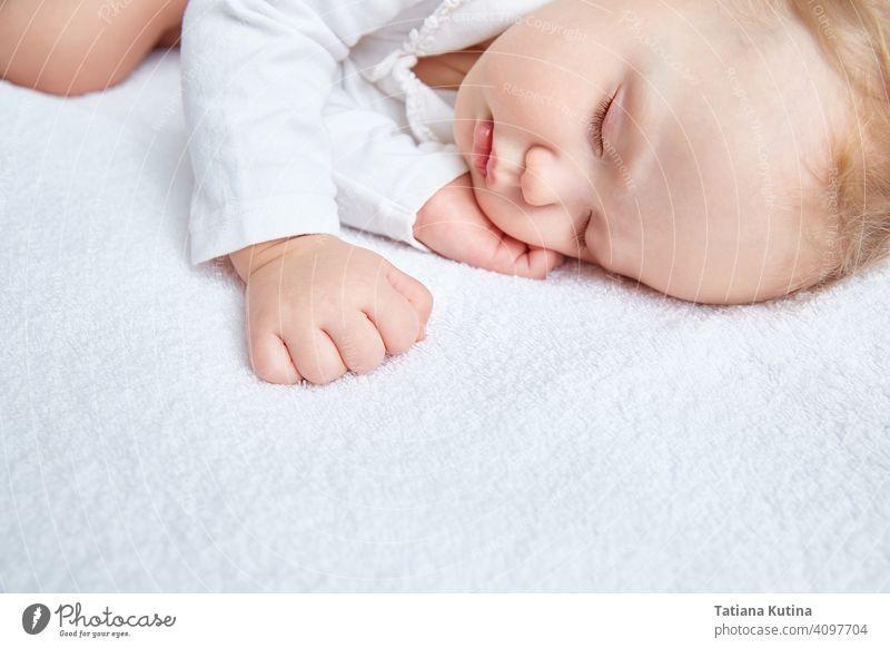 Niedliches Baby schläft süß auf weißer Bettwäsche in weißer Kleidung. Nahaufnahme. Schöne gesunde weiche Haut, lange Wimpern. Kind niedlich schlafen wenig