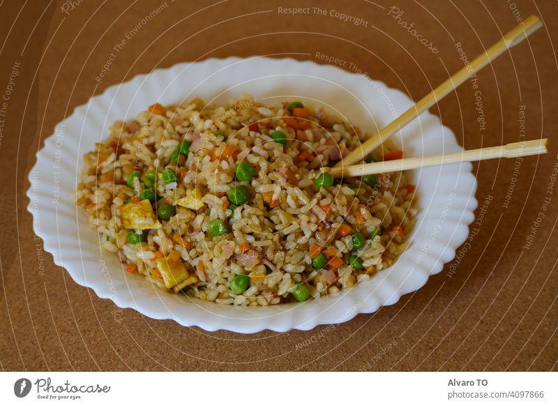 Delcious Special Gebratener Reis in einer weißen Schale und asiatische Essstäbchen Essen zubereiten Saucen Fleisch Ei speziell China Abendessen Teller gekocht