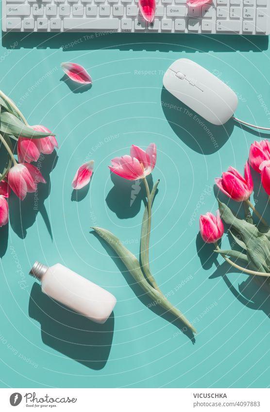 Springtime weiblichen Home-Office-Hintergrund mit rosa Tulpen, Pc, Kosmetik-Flasche und weiße Computer-Maus auf türkisblau. Ansicht von oben. Schreibtisch flach legen