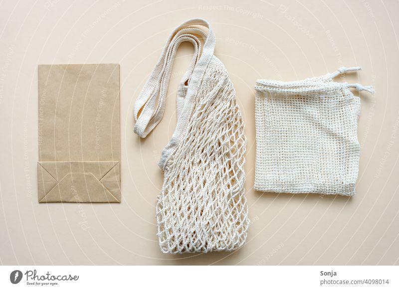 Wiedervendbare Einkaufstasche, ein Beutel und eine Papiertüte auf einem beigen Hintergrund papiertüte wiederverwendbar umweltfreundlich ökologisch