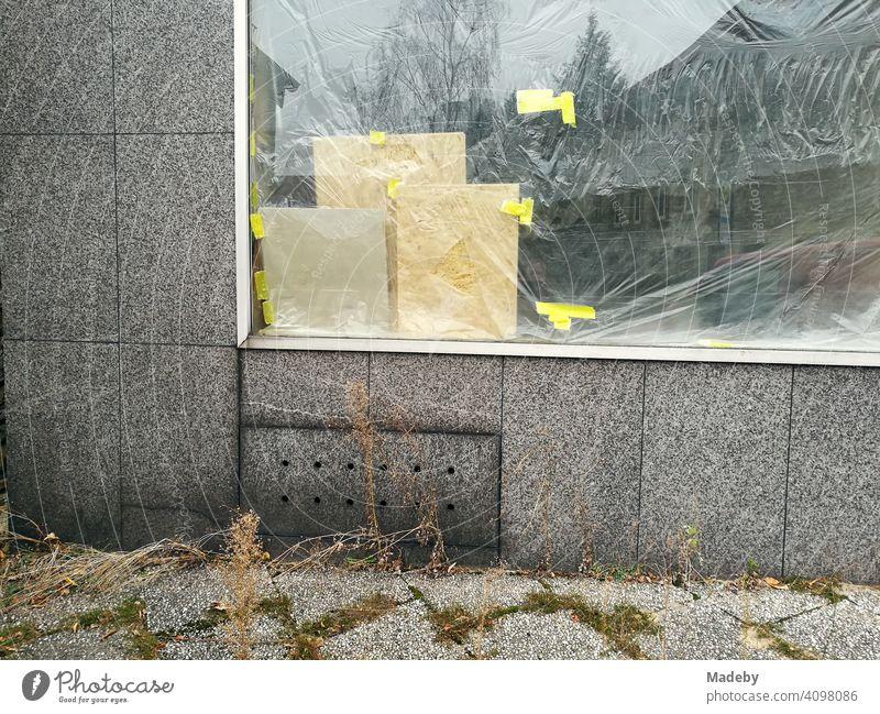 Von innen mit Folie verklebtes Schaufenster in grauer Fassade mit grauen Pflastersteinen in Oerlinghausen bei Bielefeld am Hermannsweg im Teutoburger Wald in Ostwestfalen-Lippe