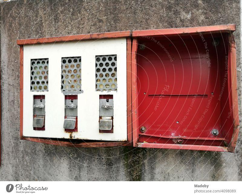 Ramponierter alter roter Kaugummiautomat auf grauer Hauswand in Lemgo bei Detmold in Ostwestfalen-Lippe Automat Rot Blech zerdellt eingedellt zerstört kaputt