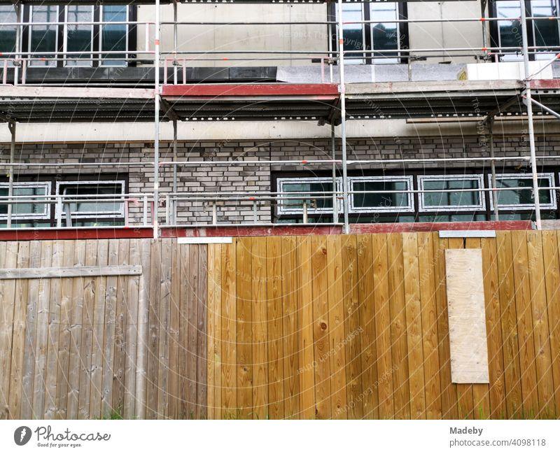 Bauzaun aus Holz vor dem Neubau eines Wohnhaus mit Baugerüst am ehemaligen Hafen in Offenbach am Main in Hessen Baustelle Holzzaun Zaun Sichtschutz Bauen