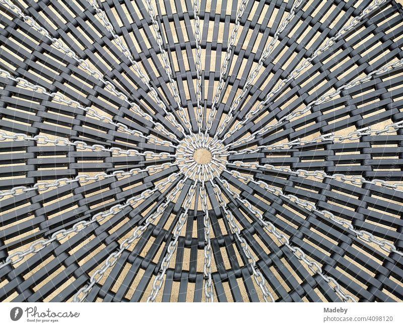 Kreisrundes Netz einer großen Schaukel auf einem Kinderspielplatz am Hafengarten am alten Hafen von Offenbach am Main in Hessen Rund Geflecht Muster Struktur
