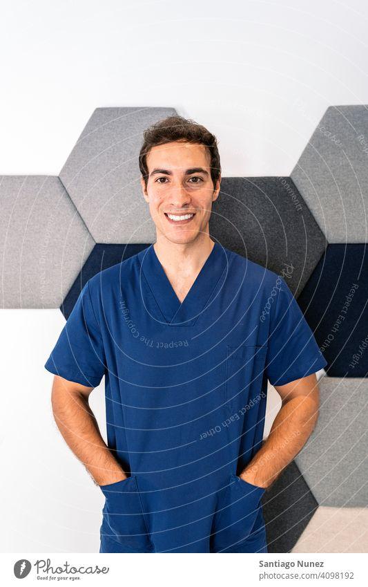 Männlicher Mitarbeiter der Zahnklinik männlich Mann Arzt Uniform Arbeitsuniform dental Klinik Dentalklinik in die Kamera schauen Lächeln im Innenbereich