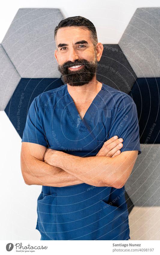 Männlicher Mitarbeiter der Zahnklinik Bartiger Mann männlich Arzt Arbeitsuniform dental Klinik Dentalklinik in die Kamera schauen Lächeln im Innenbereich