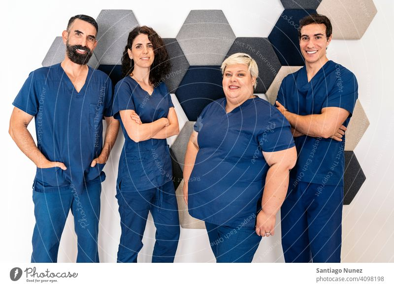 Zahnklinik Arbeitsteam Team Dentalklinik Fachleute gemischt Männer Frauen Zusammensein in die Kamera schauen bei der Arbeit Arbeitsplatz Bartiger Mann männlich