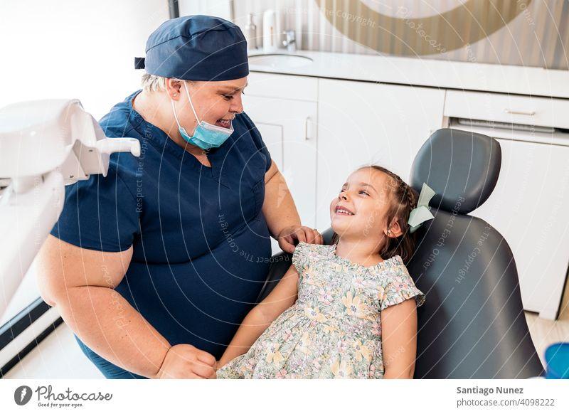 Zahnklinik Arbeiter und kleines Mädchen lächelnd die sich gegenseitig ansehen Frau geduldig Dentalklinik Lächeln Zwei Personen Vorderansicht Stehen Blick Kind