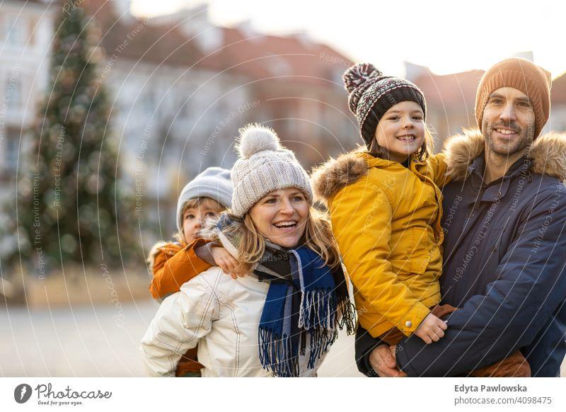 Glückliche junge Familie mit Spaß im Freien während Weihnachten Winter Mann Herbst Vater Frau Mutter Eltern Verwandte Sohn Jungen Kinder Partnerschaft