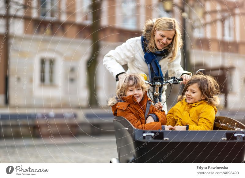 Mutter, die nach ihren Kindern schaut, die im vorderen Teil eines Lastenfahrrads fahren Lastenrad Fahrrad Fahrradfahren Verkehr Dreirad Gesundheit aktiv Zyklus