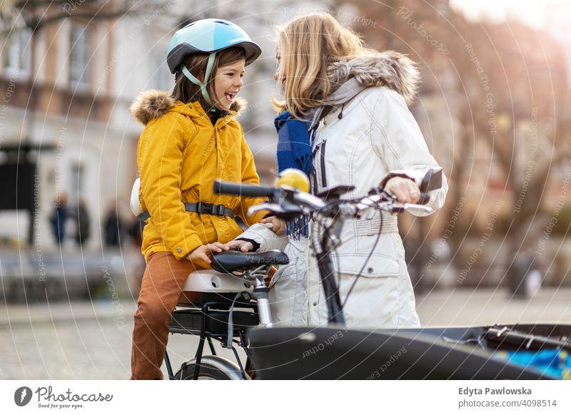 Junge Frau und ihr Sohn fahren mit dem Fahrrad in einer Stadt jung tragend Schutzhelm Fahrradfahren Winter Herbst Mutter Familie Eltern Verwandte Kind Kinder