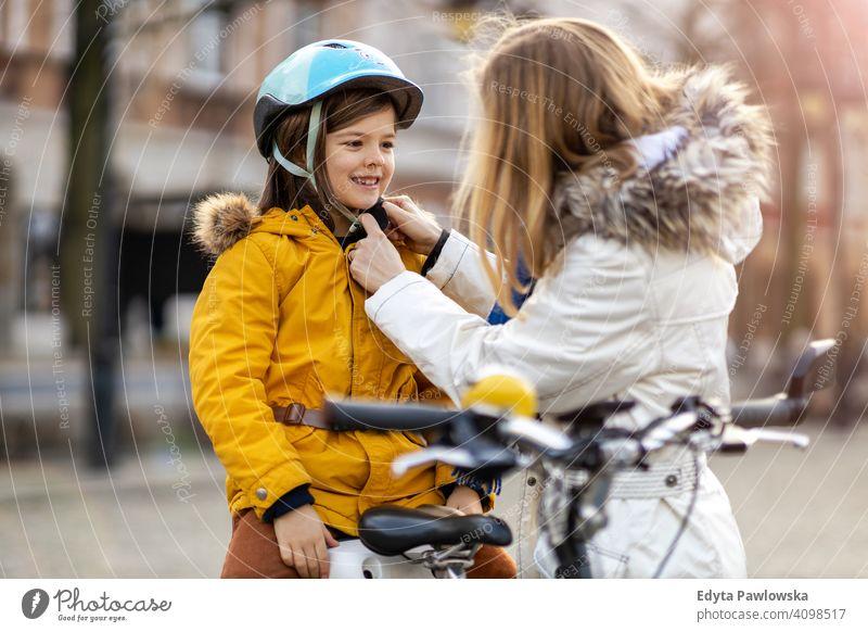 Mutter setzt ihrem Sohn einen Fahrradhelm auf jung tragend Schutzhelm Fahrradfahren Winter Frau Herbst Familie Eltern Verwandte Junge Kind Kinder Partnerschaft