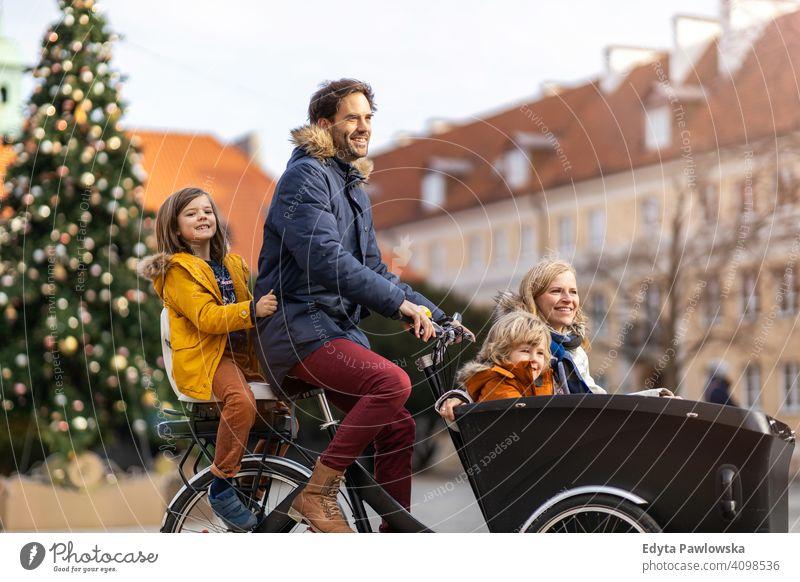 Junge Familie fährt in einem Lastenfahrrad während Weihnachten Lastenrad Fahrrad Fahrradfahren Verkehr Dreirad Gesundheit aktiv Zyklus Radfahren modern