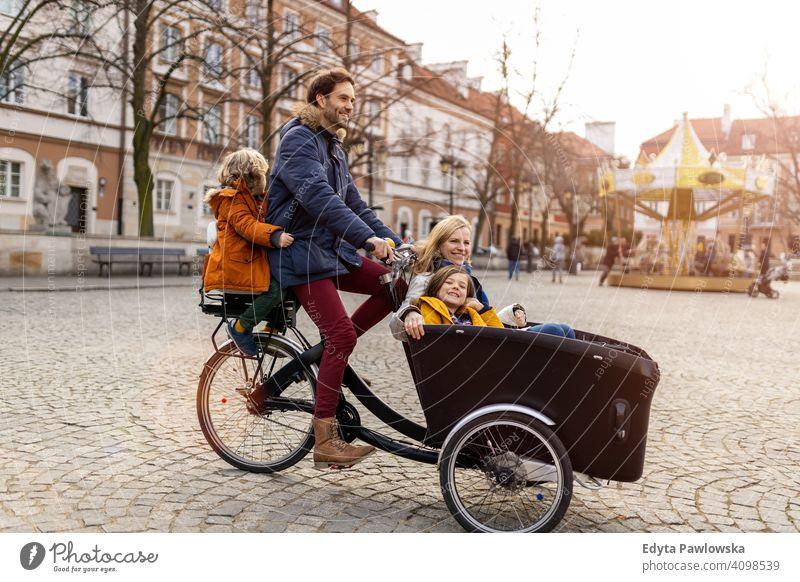 Junge Familie fahren in einem Lastenfahrrad zusammen Lastenrad Fahrrad Fahrradfahren Verkehr Dreirad Gesundheit aktiv Zyklus Radfahren modern