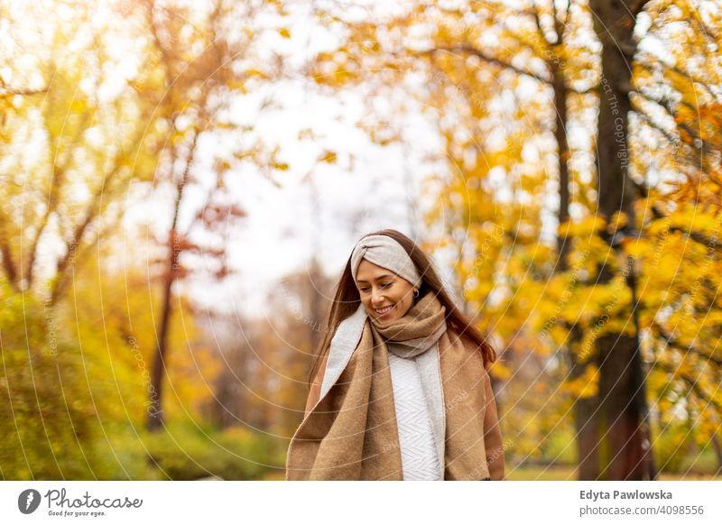Porträt einer lächelnden jungen Frau in einem Park im Herbst Natur Blätter Freiheit Gesundheit Bäume gelb Wald Saison öffentlicher Park sich[Akk] entspannen
