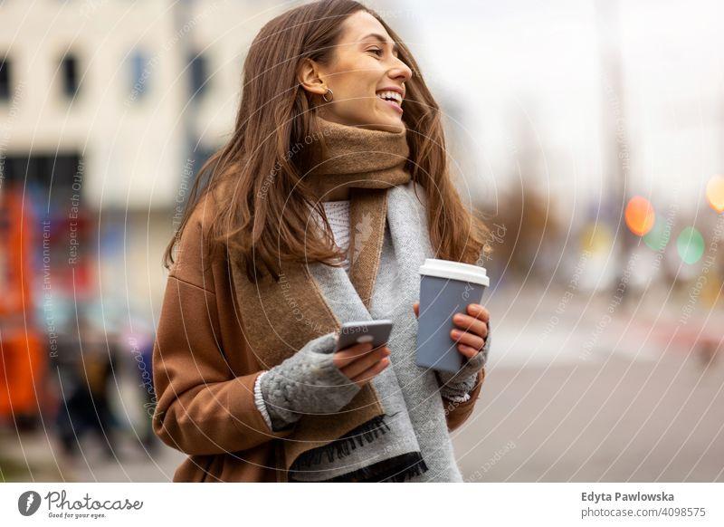 Lächelnde junge Frau mit Smartphone und Kaffeetasse im Freien in städtischer Umgebung Herbst fallen Mädchen schön Wetter Mantel Mode hübsch attraktiv