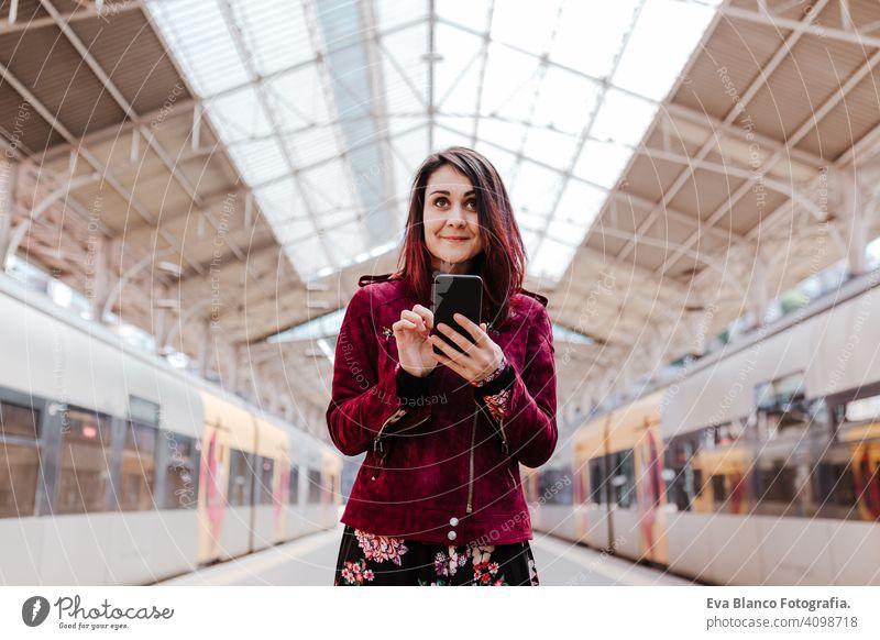 schöne kaukasische Frau im Bahnhof bereit zu reisen mit Handy. Reisen und Lifestyle-Konzept Technik & Technologie Smartphone Internet Gerät Verbindungen