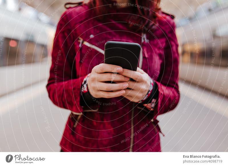Nahaufnahme von schönen kaukasischen Frau im Bahnhof bereit zu reisen mit Handy. Reisen und Lifestyle-Konzept Technik & Technologie Smartphone Internet Gerät