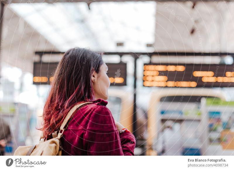 Rückenansicht von Backpacker Frau im Bahnhof warten zu reisen. Reisen und Lifestyle-Konzept Großstadt öffentlicher Verkehr Tafeln Kaukasier jung Ausflug