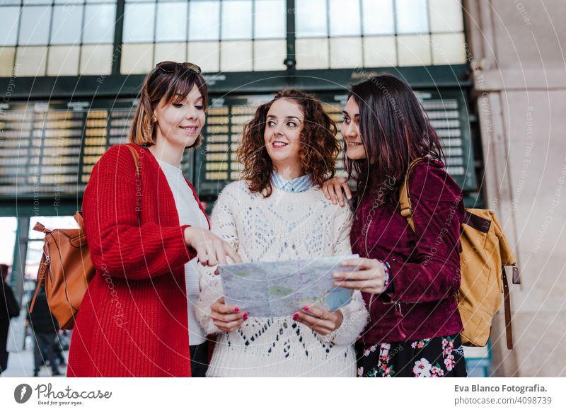 Gruppe von drei jungen kaukasischen Frauen am Bahnhof lesen eine Karte. Reisen und Freundschaft Konzept reisen Freunde Landkarte Zusammensein Spaß 3 Holzplatte
