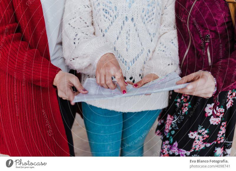 Nahaufnahme einer Gruppe von drei jungen kaukasischen Frauen am Bahnhof, die eine Karte lesen. Reisen und Freundschaft Konzept unkenntlich reisen Freunde