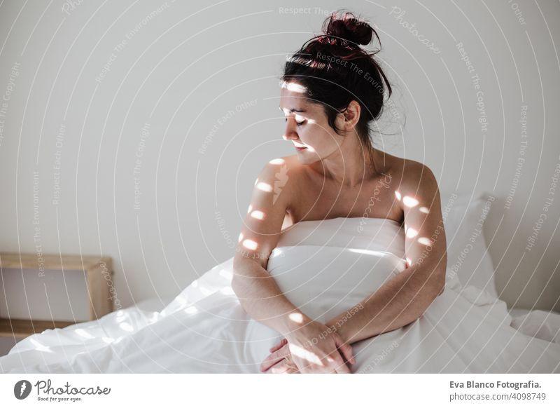 attraktive junge kaukasische Frau entspannt gut im Bett während der Morgenzeit. Dame genießt frische weiche Bettwäsche Bettwäsche und Matratze im Schlafzimmer