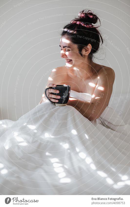 attraktive junge kaukasische Frau entspannt gut im Bett während der Morgenzeit. Dame genießt Tasse Kaffee im Schlafzimmer Frühstück trinken Getränk heiß Tee