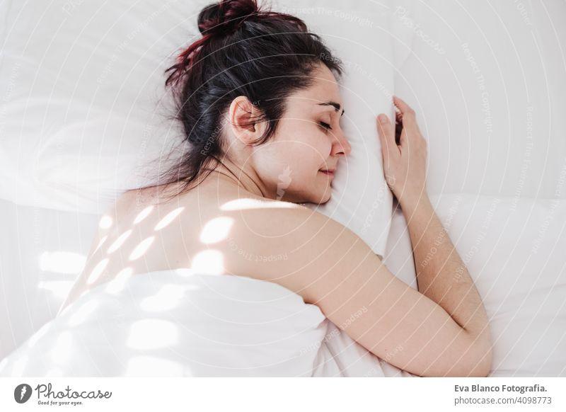 Draufsicht auf attraktive junge Frau gut schlafen im Bett umarmt weichen weißen Kissen. Mädchen ruht, gute Nacht schlafen Konzept. Lady genießt frische weiche Bettwäsche Bettwäsche und Matratze im Schlafzimmer