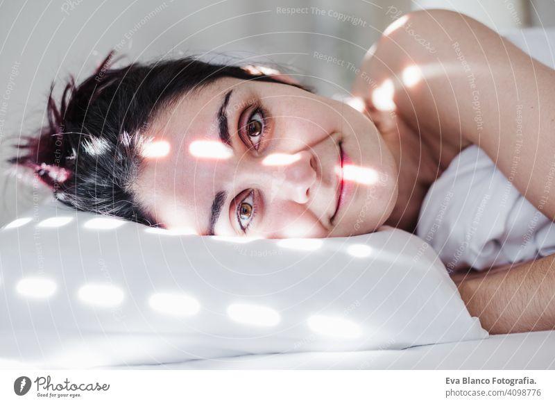 Porträt der attraktiven jungen kaukasischen Frau entspannt im Bett während der Morgenzeit. Dame genießt frische weiche Bettwäsche Bettwäsche und Matratze im Schlafzimmer