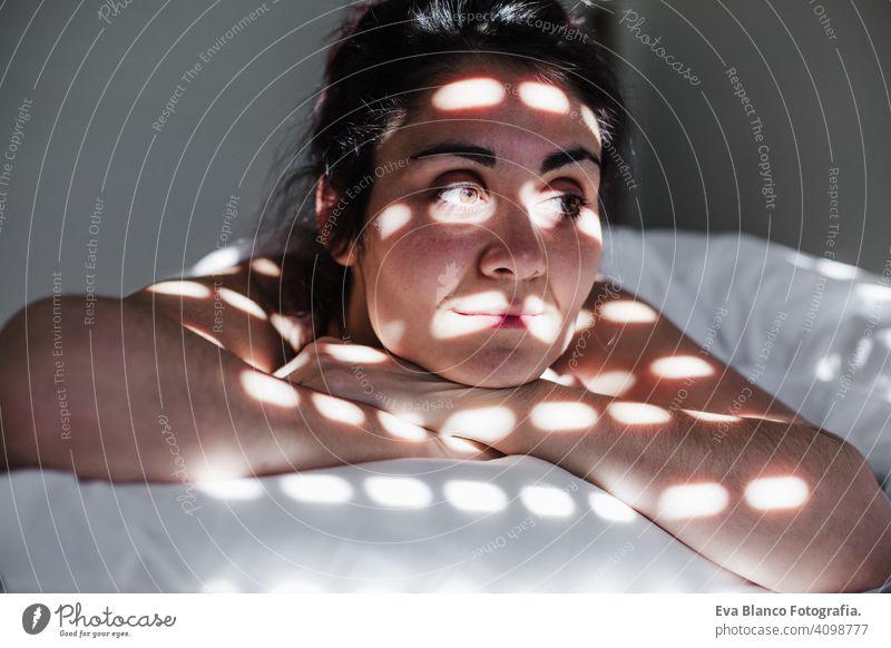 Porträt der attraktiven jungen kaukasischen Frau entspannt im Bett während der Morgenzeit. Lady genießt frische weiche Bettwäsche Bettwäsche und Matratze im Schlafzimmer. Blinde Schatten auf dem Gesicht