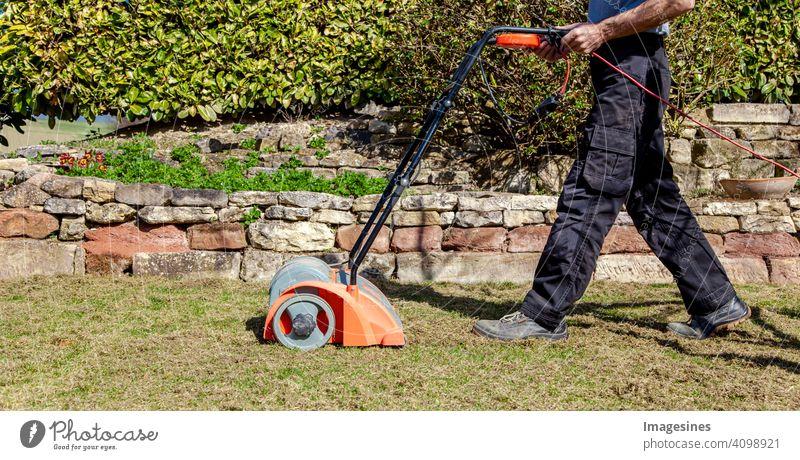 Gartenarbeit im Frühling. Vertikutieren, Rasen lüften im Garten zur Verbesserung der Rasenqualität im Frühjahr. männlich Arbeiter Mann Gärtner Bodenbelüftung