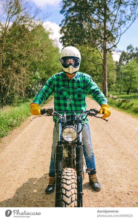 Mann mit Helm auf einem Custom-Motorrad Biker trotzig benutzerdefiniert altehrwürdig Fahrrad retro Reiter Fahrzeug Verkehr posierend jung Erwachsener Menschen