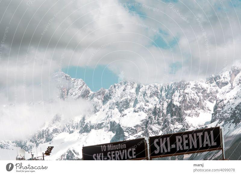 Aus, vorbei. Corona hat das Ski-Mieten an den Rand gedrängt. Werbetafeln vor verschneitem Dachstein. Skimiete Mietski Skiservice Bergwelt Alpen Gipfel