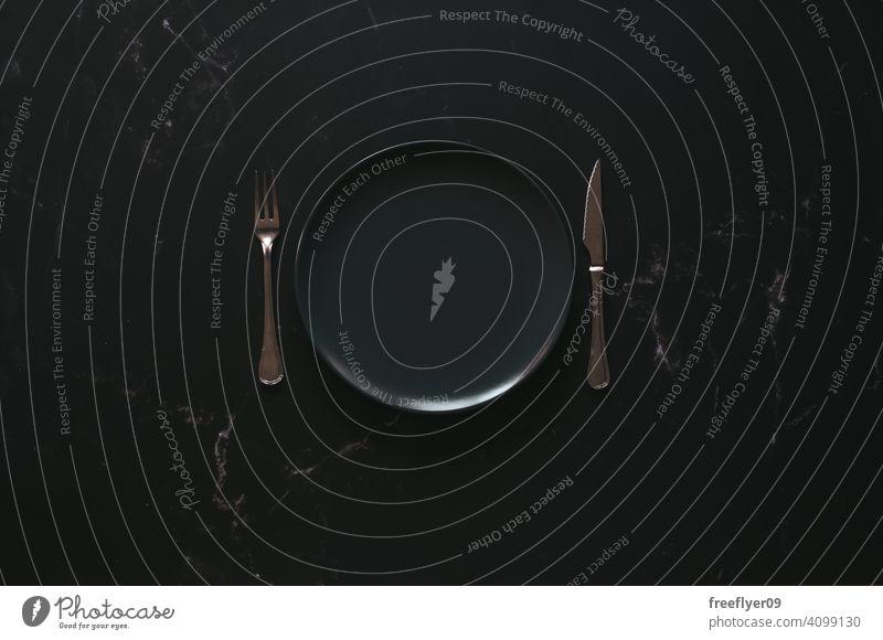 Mockup eines leeren Tellers vor einem luxuriösen Hintergrund Attrappe Besteck schwarz dunkel Reichtum luxuriöses Lebensmittel Textfreiraum Murmel Stein