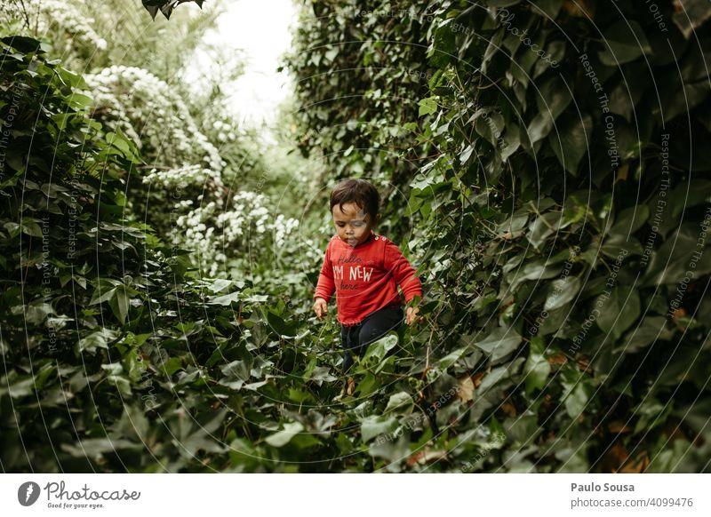 Kind läuft auf Laubpflanzen grün Grünpflanze Laubwerk 1-3 Jahre Kaukasier rot Pflanze Kleinkind Farbfoto Außenaufnahme Mensch Kindheit Natur Tag erkunden