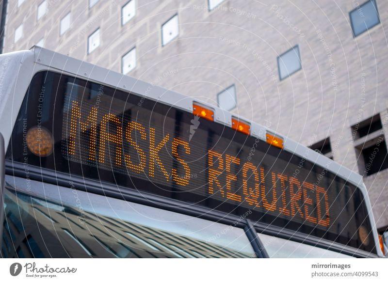 """das vordere Dach eines Stadtbusses mit einem beleuchteten Schild mit der Aufschrift """"Masken erforderlich"""" Corona-Virus Personenbus Transport Rabenvögel 19"""