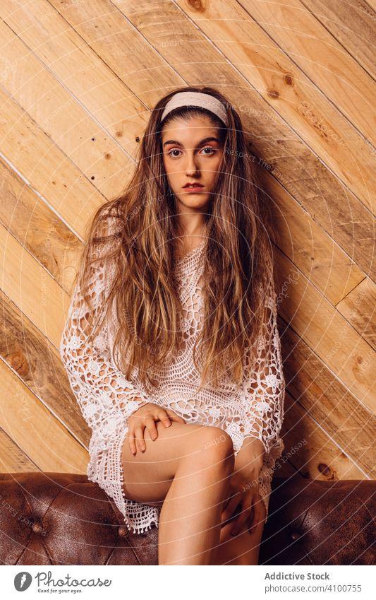 Junge Frau in weißem Kleid sitzt auf einer Couch jung Sitzen Liege Innenbereich Hipster braun Beine Mode Porträt Person hölzern Raum Menschen Mädchen Sofa Holz