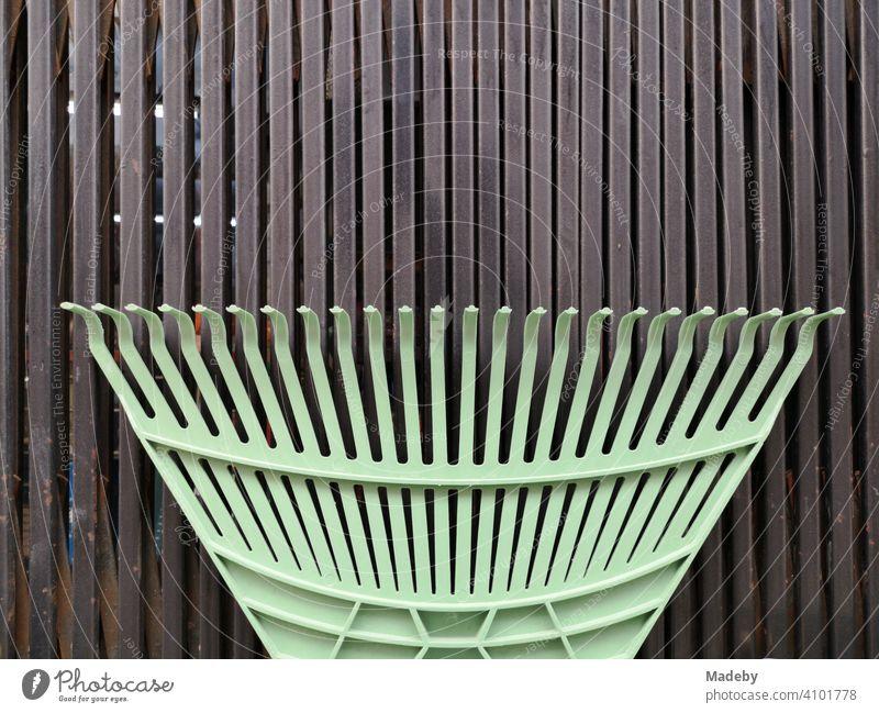 Grüner Rechen aus Kunststoff für den Garten vor braunem Paneel aus Holz in der Altstadt von Alacati bei Cesme am Mittelmeer in der Provinz Izmir in der Türkei