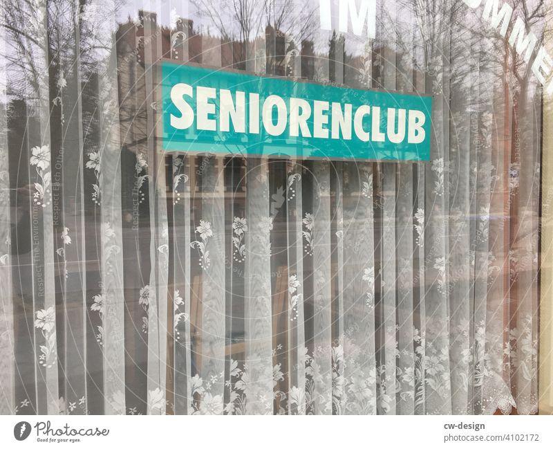 Schild vom ˋSeniorenclubˋmit Gardine im Schaufenster Ladengeschäft schaufensterscheibe Schaufenstergestaltung schaufensterdeko Schaufenster Fassade