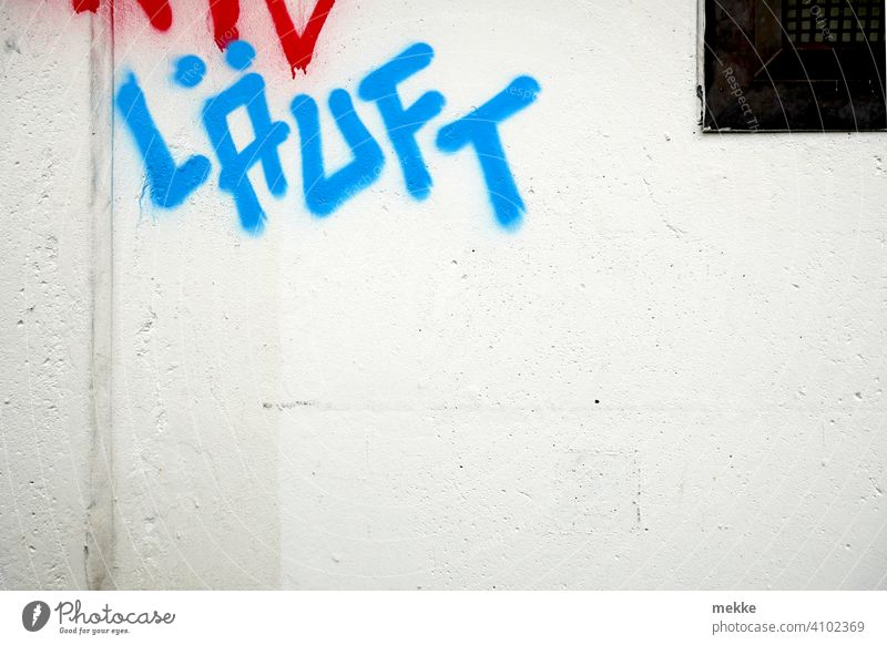 Läuft Grafitti auf weißer Hauswand grafitti schrift blau wandmalerei Text botschaft farbe Deutsch gesprayt grafitto mauer urban stadt slogan straße