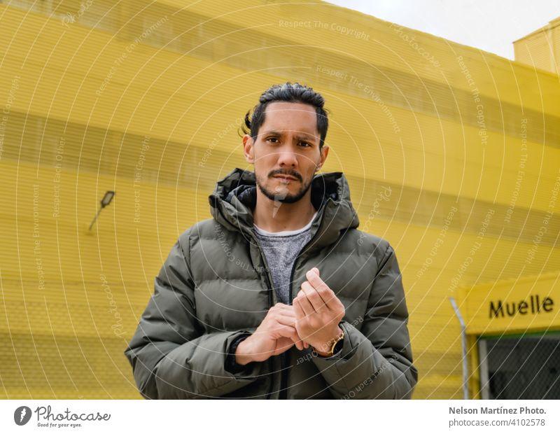 Porträt eines hispanischen Mannes vor einem gelben Hintergrund lokales Geschäft Sonnenlicht Tag Business eine Person Hispanische Ethnizität selbstbewusst