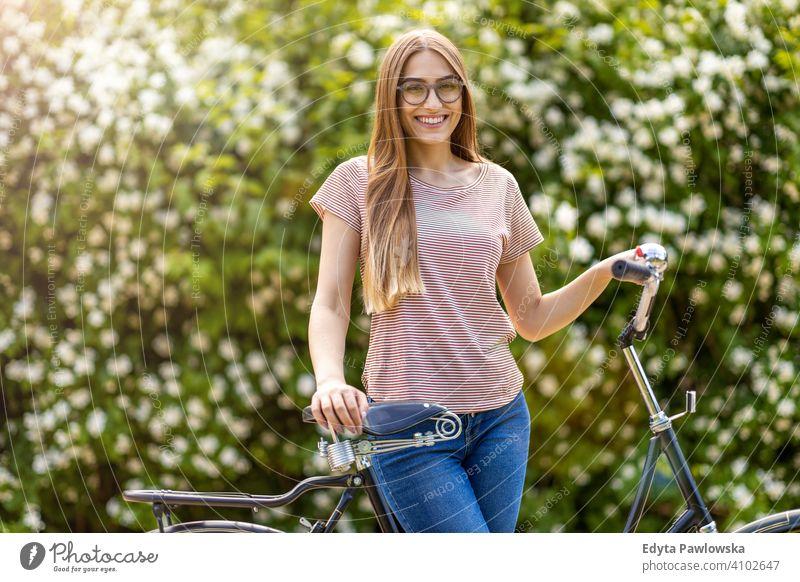 Junge Frau geht für eine Fahrradtour im Park aktiv in Bewegung Pendler Verkehr Zyklus Fahrradfahren Radfahren Gesundheit umweltfreundlich ökologisch genießend
