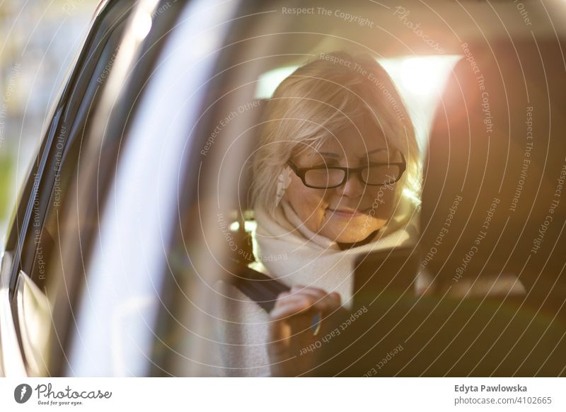 Ältere Frau mit Smartphone auf dem Rücksitz eines Autos Menschen eine Person Senior reif Rentnerinnen in den Ruhestand getreten alt älter graues Haar Kaukasier