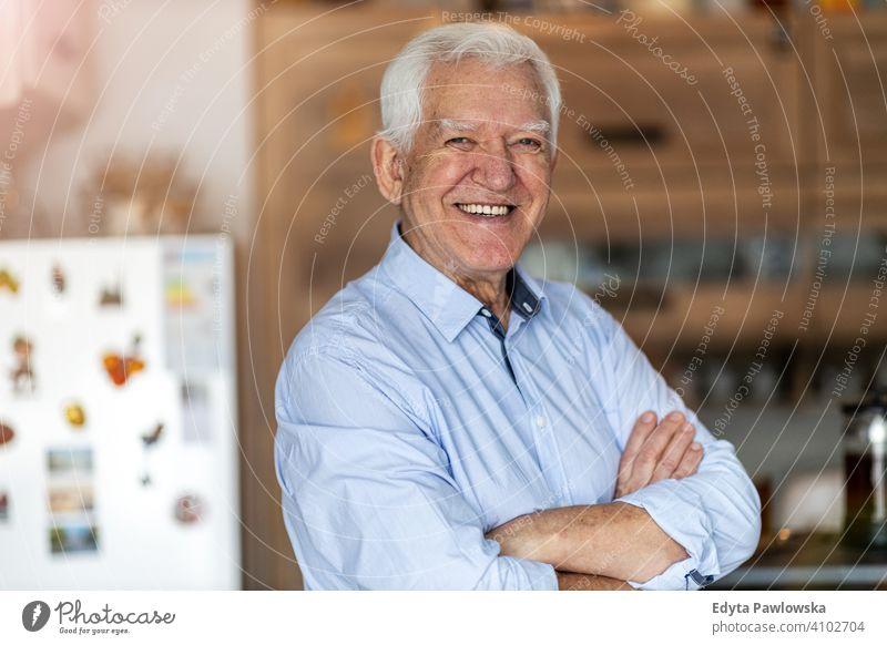 Lächelnder älterer Mann in seinem Haus Menschen eine Person Senior reif Rentnerinnen in den Ruhestand getreten alt graues Haar Kaukasier Erwachsener Lifestyle