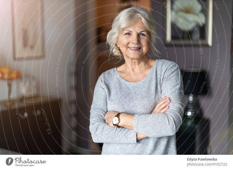 Lächelnde Seniorin in ihrem Haus Frau Menschen eine Person reif Rentnerinnen in den Ruhestand getreten alt älter graues Haar Kaukasier Erwachsener Lifestyle