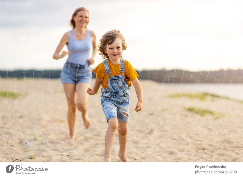 Mutter und ein Kind, die einen Tag am Strand genießen MEER See Feiertage Urlaub Natur Sommer Familie Eltern Sohn Junge Kinder Zusammensein