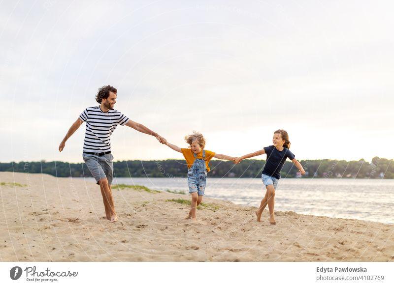 Vater mit zwei Kindern, die einen Tag am Strand genießen MEER See Feiertage Urlaub Natur Sommer Familie Eltern Sohn Junge Zusammensein
