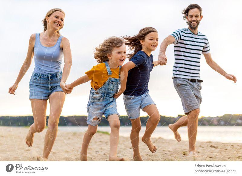 Junge Familie mit Spaß im Freien am Strand MEER See Feiertage Urlaub Natur Sommer Eltern Sohn Kinder Zusammensein Zusammengehörigkeitsgefühl Liebe Menschen